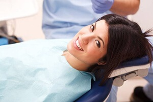 Young woman in dental chair with attractive smile