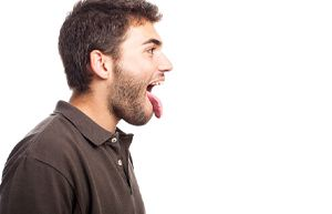 side view of man sticking tongue out