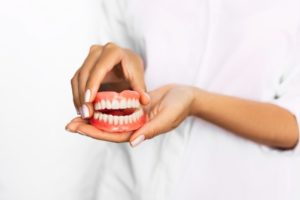 Close up of person holding upper and lower dentures